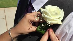 Woman pinning corsage on vest