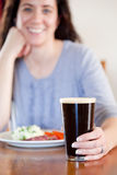 Woman with pint. Young woman holding a pint with lunch at a pub Stock Photo