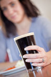 Woman with pint. Young woman holding a pint with lunch at a pub Stock Image