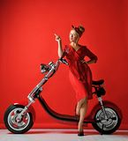 Woman pinup style ride new electric car motorcycle bicycle scooter present for new year 2019 pointing finger up stock image
