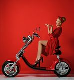 Woman pinup style ride new electric car motorcycle bicycle scooter present for new year 2019 in red dress pointing hands up. On red background royalty free stock image
