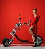 Woman pinup style ride new electric car motorcycle bicycle scooter present for new year 2019. In red dress on red background stock photos
