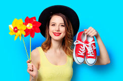 Woman with pinwheels and gumshoes. Portrait of young smiling red-haired white european woman in hat with pinwheels toy and red gumshoes on blue background Stock Photo