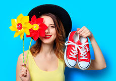 Woman with pinwheels and gumshoes. Portrait of young smiling red-haired white european woman in hat with pinwheels toy and red gumshoes on blue background Stock Photos