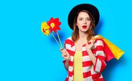 Woman with pinwheels and shopping bags. Portrait of young surprised red-haired white european woman in hat and red striped shirt with pinwheels and shopping bags Royalty Free Stock Images