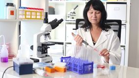 Woman with a pipette. And a microscope in a lab stock video footage
