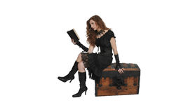 Woman pirate reading a book. Beautiful young woman pirate reading a book treasure chest Royalty Free Stock Photo