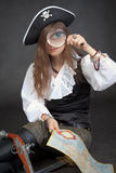 Woman-pirate with sea map and magnifier glass Royalty Free Stock Photography