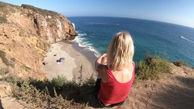 Woman at Pirates Cove promontory. Caucasian female looks Pirates Cove promontory Beach from Point Dume promontory on Malibu coast in CA, United States. Carefree stock video