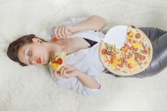 Woman with pizza. Beautiful overeat businesswoman lying with pizza pieces Stock Photo