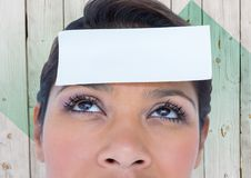Woman with placard on forehead against wooden background Stock Photo
