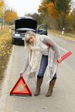 Woman places an emergency sign. To warn other drivers stock photography