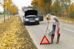 Woman places an emergency sign. To warn other drivers stock photos