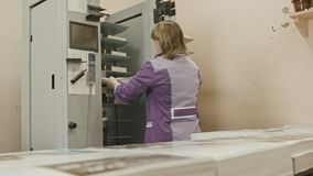 Woman places a sheet of paper for completing the magazine on polygraph machine in printing house stock footage