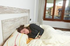 Woman placidly sleeping in bed in her large bedroom. Woman placidly sleeping in bed in her large bedroom happy lifestyle lazy pillow young rest relax person stock photos