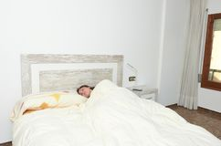 Woman placidly sleeping in bed in her large bedroom. Woman placidly sleeping in bed in her large bedroom happy lifestyle lazy pillow young rest relax person royalty free stock image