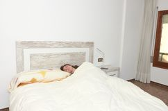 Woman placidly sleeping in bed in her large bedroom. Woman placidly sleeping in bed in her large bedroom happy lifestyle lazy pillow young rest relax person royalty free stock photos