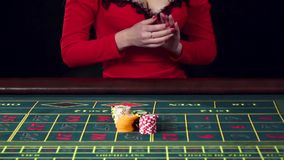 Woman placing an all in bet in roulette. Black stock video footage