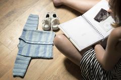 Woman placing baby`s sonogram into baby`s first year memory book. Baby clothes and sneakers laying on the floor stock photo