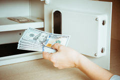 Woman placing cash in safety deposit box in hotel vault Stock Image