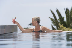 Woman Placing Daiquiri On Poolside. Happy middle aged woman placing daiquiri on poolside from pool Stock Photos