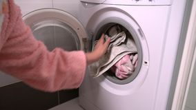 Woman placing dirty laundry in a washing machine. Woman placing dirty laundry into a front loading a washing machine then closing the door once it is full stock footage