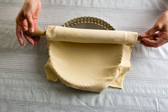 Woman placing dough stretched over a mold. Woman placing stretched raw dough with a rolling pin on a baking quiche Royalty Free Stock Photography