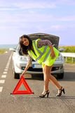 Woman placing emergency triangle Stock Images