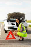 Woman placing emergency triangle Stock Image