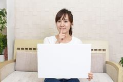 Woman placing finger on lips. Asian woman holding a whiteboard stock photo