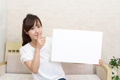 Woman placing finger on lips. Asian woman holding a whiteboard royalty free stock images