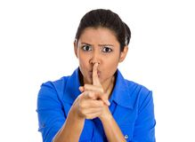 Woman placing finger on lips, pointing at you as if to say, shhhhh, quiet. Closeup of serious woman placing finger on lips, pointing at you as if to say, shhhhh Royalty Free Stock Photos