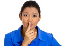 Woman placing finger on lips, pointing at you as if to say, shhhhh, quiet. Closeup of serious woman placing finger on lips, pointing at you as if to say, shhhhh Stock Image