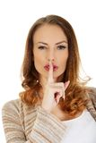 Woman placing finger on lips. Stock Image