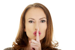 Woman placing finger on lips. Royalty Free Stock Photo