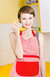 Cute girl talking on fruit phone in kitchen Stock Image