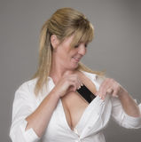 Woman placing phone into her bra Royalty Free Stock Photos