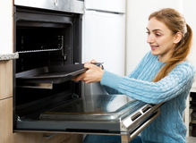 Woman placing roasting tray in kitchen oven Stock Photo