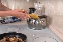 Woman placing spaghetti into a pot Stock Photos