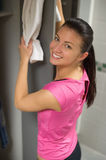 Woman placing towel on open locker door Royalty Free Stock Image