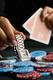 Woman placing watch on pile of gambling chips on table, close-up Royalty Free Stock Images
