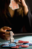 Woman placing watch on pile of gambling chips on table, mid section Royalty Free Stock Image
