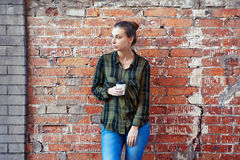 Woman in a plaid green shirt standing disposable coffee cup on the background brick wall Royalty Free Stock Photos