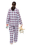 Woman in plaid pajamas goes to bed, in hands teddy bear Royalty Free Stock Images