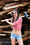 Woman in plaid shirt with axe Stock Image