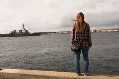 Woman in Plaid Staring at Ship on Ocean. Woman with long auburn hair, staring out at the ocean as a ship passes by in San Diego, California Royalty Free Stock Images