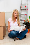Woman with a plan in the new apartment move. Royalty Free Stock Photo