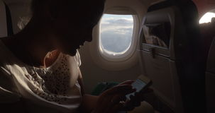 Woman in the plane changing phone settings stock footage