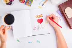 Woman planing date and sex in her personal organizer. Hands with pencil and coffee cup under notebook with heart, sex word, angels. Stauette on the working Stock Images
