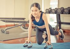 Woman planking with one leg on fitness floor. Woman is planking with one leg on fitness floor Royalty Free Stock Images